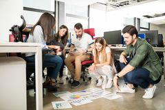 Business team reviewing some performance charts. Group of five business people looking at graphs laying on office floor royalty free stock photo