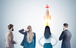 Business team and rocket launch, toned. Rear view of a business team members looking at a rocket launch while standing near a gray wall. Toned image royalty free stock photos