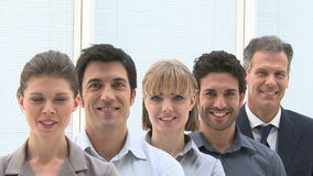 Business team in a row. Happy smiling business team standing in a row at office. Businesspeople looking at camera with satisfaction. Proud businesswomen and