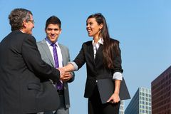 Business team shaking hands over deal outdoors. Royalty Free Stock Images