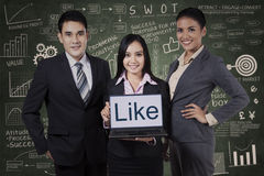 Business team showing like on laptop. Over chalkboard background royalty free stock photos