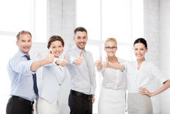 Business team showing thumbs up in office Stock Photo
