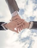 Business team showing unity with hands together. Bottom view of business team showing unity with hands together over blue sky background Stock Image