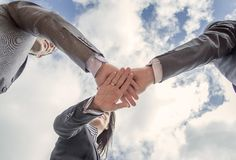 Business team showing unity with hands together stock photos