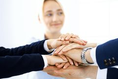 Business team showing unity with their hands together. Group of people joining hands and representing concept of. Friendship, teamwork and partnership royalty free stock photography