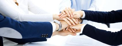 Business team showing unity with their hands together. Group of people joining hands and representing concept of. Friendship, teamwork and partnership royalty free stock image