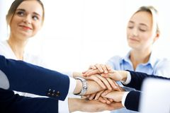 Business team showing unity with their hands together. Group of people joining hands and representing concept of. Friendship, teamwork and partnership royalty free stock images