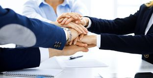 Business team showing unity with their hands together. Group of people joining hands and representing concept of. Friendship, teamwork and partnership stock photos
