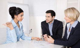 Business team sitting around a table in a meeting talking togeth Stock Image