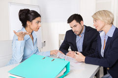 Business team sitting around a table in a meeting talking togeth Royalty Free Stock Photo