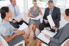 Business team sitting in circle and discussing. In the office royalty free stock photography