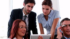 Business team sitting on couch having a meeting using tablet. In the office stock footage