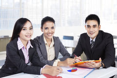 Business team sitting in office and smiling Stock Images