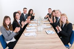 Business team sitting at table and applauding. During Presentation Stock Photography
