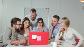 Team brainstorming in front of a laptop. Business team of six people sitting in front of a laptop in the office, Man describing his business project to a team stock footage
