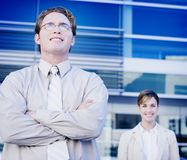 Business team smiling. Business man and woman standing together in front of a blue business building Stock Photos