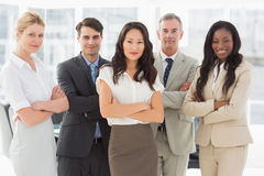 Business team smiling at camera with arms crossed Royalty Free Stock Photos
