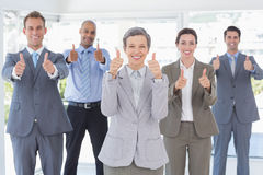 Business team smiling at camera showing thumbs up Stock Image