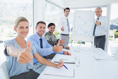 Business team smiling at camera showing thumbs up Royalty Free Stock Images