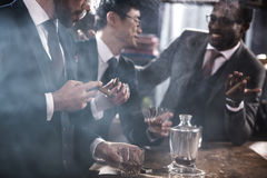 Business team spending time, smoking cigars and drinking whiskey. Multicultural business team spending time, smoking cigars and drinking whiskey Royalty Free Stock Photography
