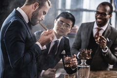 Business team spending time, smoking cigars and drinking whiskey Stock Photos