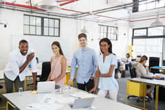 Business team stand at desk in an office looking to camera Royalty Free Stock Photo
