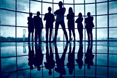 Business team. Standing against window with leader in front royalty free stock photo