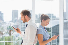 Business team standing back to back and texting Stock Photos