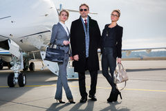 Business team standing in front of private jet Stock Photography