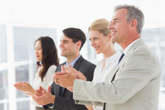 Business team standing in a line applauding Stock Photography