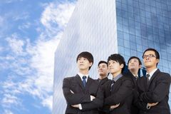 Business team standing before the modern building. Young asian business team standing before the modern building Royalty Free Stock Photos