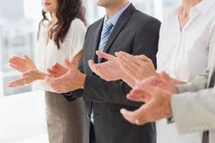 Business team standing in a row applauding Royalty Free Stock Photography