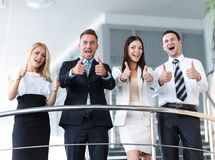 Business team standing on the terrace and shows thumb up. Royalty Free Stock Photography