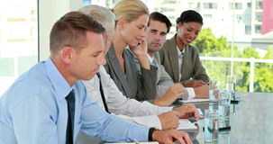 Business team taking notes during conference while colleague having a phone call stock footage
