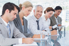 Business team taking notes during conference Stock Photo