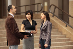 Business team of talking with client. About a deal outdoors in front of an office building on stairs in the city Stock Image