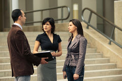 Business team talking with client. Business team at meeting outdoors talking with client in front of an office building on the stairs Stock Photos