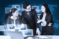 Business team talking financial statistics Stock Image