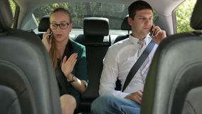 Business team talking on phones in car. Successful business team in formalwear sitting at the backseat of car, using smartphones during business trip. Two stock video footage