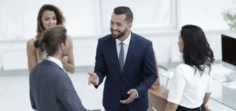 Business team talking, standing in office. Successful business team talking, standing in office Stock Photo
