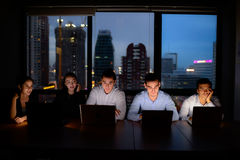 Business team, three man and two woman working with computer overtime at night Stock Photos