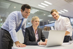 A business team of three in office and planning work Stock Image
