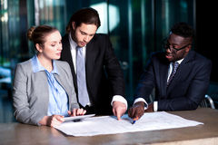 Business team of three reviewing project plan Royalty Free Stock Photo