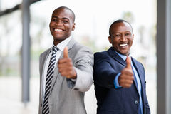Business team thumbs up. Cheerful african business team giving thumbs up stock image