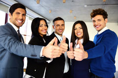 Business team with thumbs up sign. Cheerful young business team with thumbs up sign Royalty Free Stock Images