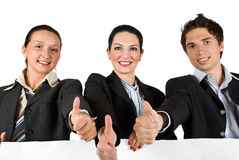 Business team with thumbs up and white sign Stock Photo