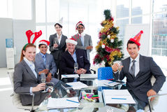Business team toasting with Champagne. Happy business team toasting with Champagne at a Christmas party in the office Royalty Free Stock Photography