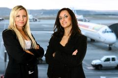 Business team travel. Two businesswomen, standing in the departure hall of an airport, waiting to catch her flight for her business travel. Concept of business Royalty Free Stock Photo