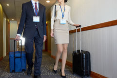 Business team with travel bags at hotel corridor. Business trip and people concept - men and women with travel bags and conference badges at hotel corridor Stock Photo