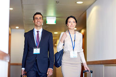Business team with travel bags at hotel corridor. Business trip and people concept - men and women with travel bags and conference badges at hotel corridor Royalty Free Stock Image